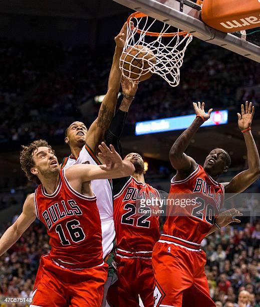 Forward Khris Middleton of the Milwaukee Bucks scores over center Pau Gasol forward Taj Gibson and forward Tony Snell of the Chicago Bulls in the...