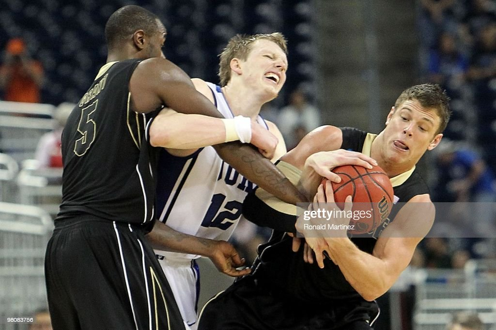Forward Kyle Singler of the Duke Blue Devils is fouled by Keaton Grant and Chris Kramer of the Purdue Boilermakers during the south regional...