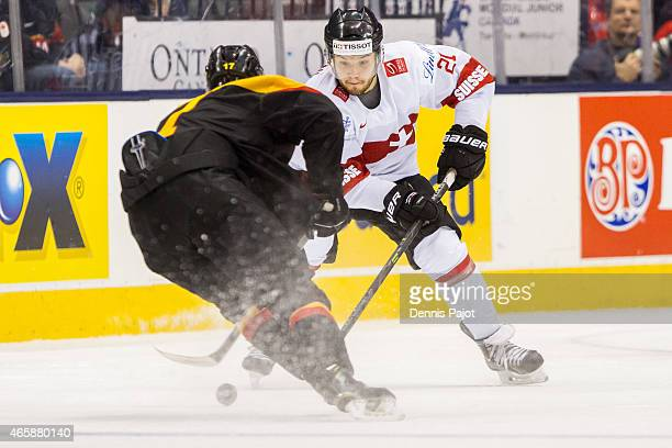 Forward Luca Fazzini of Switzerland battles for the puck against defenceman forward Frederik Tiffels of Germany during the 2015 IIHF World Junior...