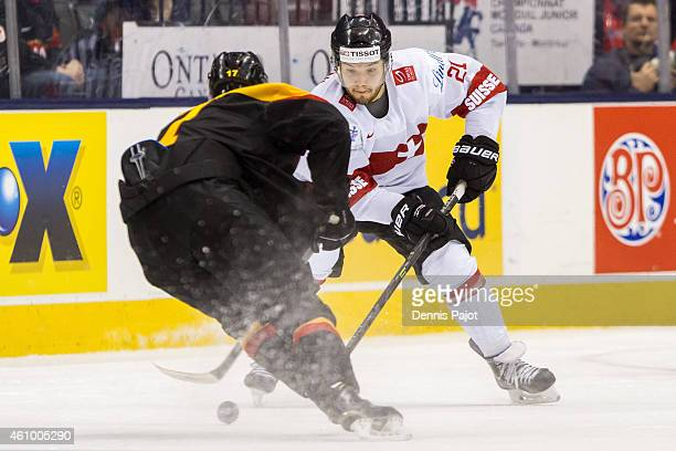 Forward Luca Fazzini of Switzerland moves the puck against forward Frederik Tiffels of Germany during the 2015 IIHF World Junior Championship on...