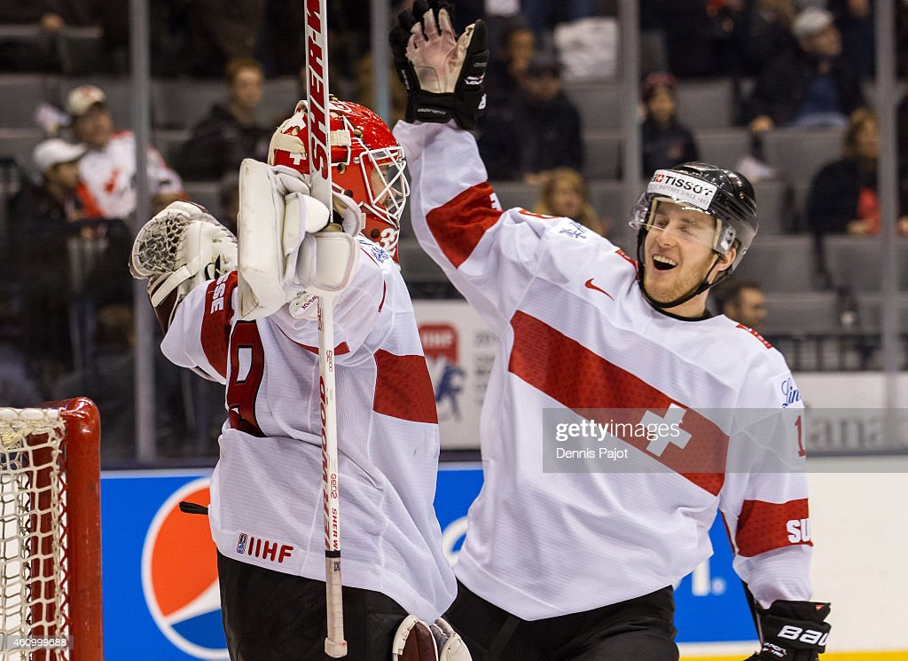 Forward Luca Hischier #13 celebrates with goaltender Gauthier Descloux #29 of Switzerland after a win over Germany during the 2015 IIHF World Junior Championship on January 03, 2015 at the Air Canada Centre in Toronto, Ontario, Canada.
