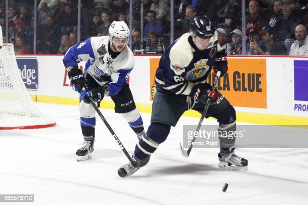 Forward Luke Boka of the Windsor Spitfires moves the puck against defenceman Simon Bourque on May 19 2017 during Game 1 of the Mastercard Memorial...