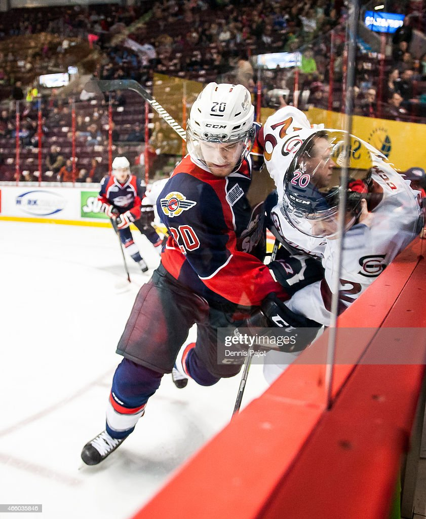 Forward Luke Cairns #20 of the Guelph Storm battles for the puck against defenceman Andrew Burns #20 of the Windsor Spitfires on March 12, 2015 at the WFCU Centre in Windsor, Ontario, Canada.