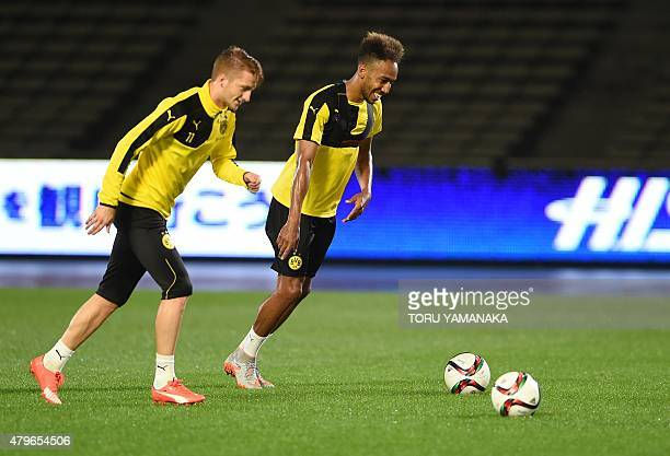 Forward Marco Reus and PierreEmerick Aubameynag of Germany's football club Borussia Dortmund kick balls during a training session after their arrival...