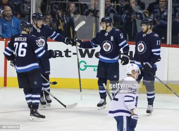 Forward Mark Scheifele of the Winnipeg Jets celebrates his goal with teammates forward Blake Wheeler forward Patrik Laine and forward Adam Lowry...