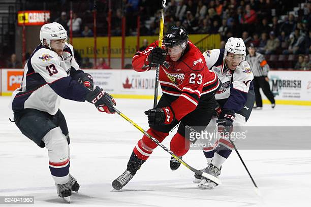 Forward Matt Schmalz of the Owen Sound Attack moves the puck against forward Gabriel Vilardi and defenceman Logan Stanley of the Windsor Spitfires on...