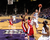Forward Michael Beasley of the Kansas State Wildcats drives puts up a shot against pressure from Nebraska Cornhuskers guard Ryan Anderson and forward...