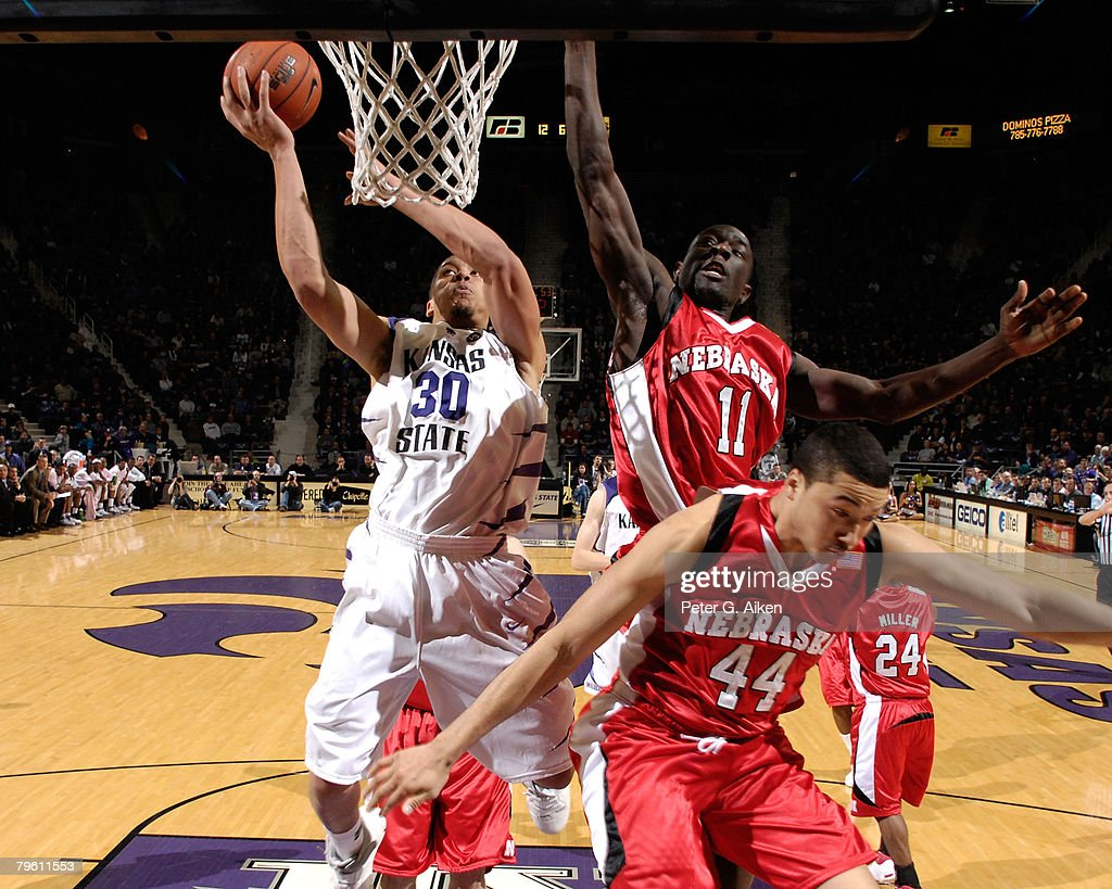 Forward Michael Beasley of the Kansas State Wildcats drives to the basket against pressure from Nebraska Cornhuskers guard Ade Dagunduro and guard...
