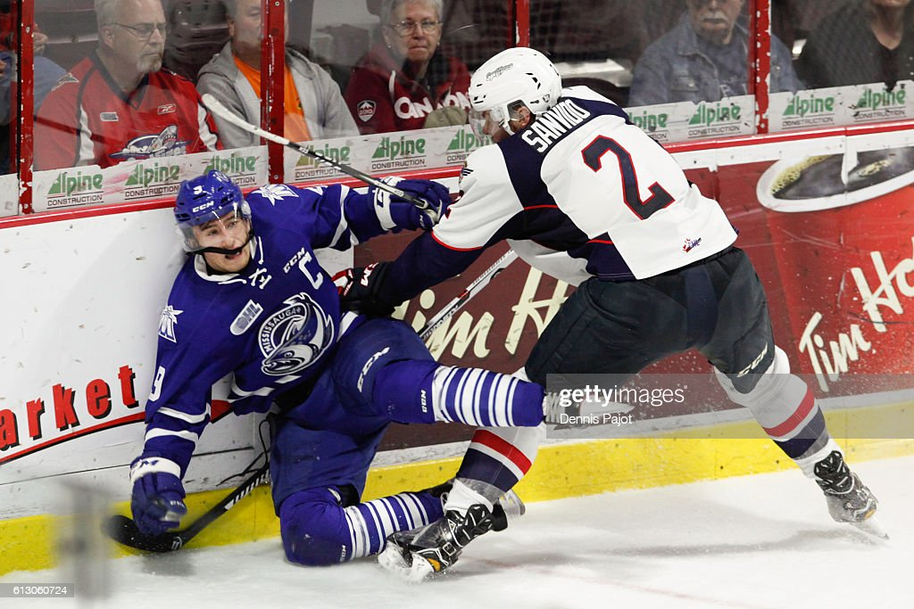 Forward Michael McLeod #9 of the Mississauga Steelheads is checked into the boards on a hit from defenceman Patrick Sanvido #2 of the Windsor Spitfires on October 6, 2016 at the WFCU Centre in Windsor, Ontario, Canada.