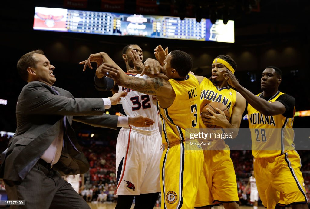 Forward Mike Scott #32 of the Atlanta Hawks pushes forward George Hill #3 of the Indiana Pacers in the face while Indiana Pacers head coach Frank Vogel, center <a gi-track='captionPersonalityLinkClicked' href=/galleries/search?phrase=Ian+Mahinmi&family=editorial&specificpeople=740196 ng-click='$event.stopPropagation()'>Ian Mahinmi</a> #28 and forward <a gi-track='captionPersonalityLinkClicked' href=/galleries/search?phrase=Chris+Copeland&family=editorial&specificpeople=833969 ng-click='$event.stopPropagation()'>Chris Copeland</a> #22 try to break it up in Game 6 of the Eastern Conference Quarterfinals during the 2014 NBA Playoffs at Philips Arena on May 1, 2014 in Atlanta, Georgia.