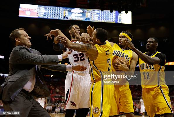 Forward Mike Scott of the Atlanta Hawks pushes forward George Hill of the Indiana Pacers in the face while Indiana Pacers head coach Frank Vogel...