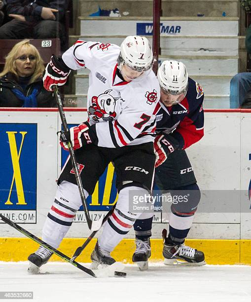 Forward Mikkel Aagaard of the Niagara Ice Dogs battles for the puck against forward Lucas Venuto of the Windsor Spitfires on February 15 2015 at the...