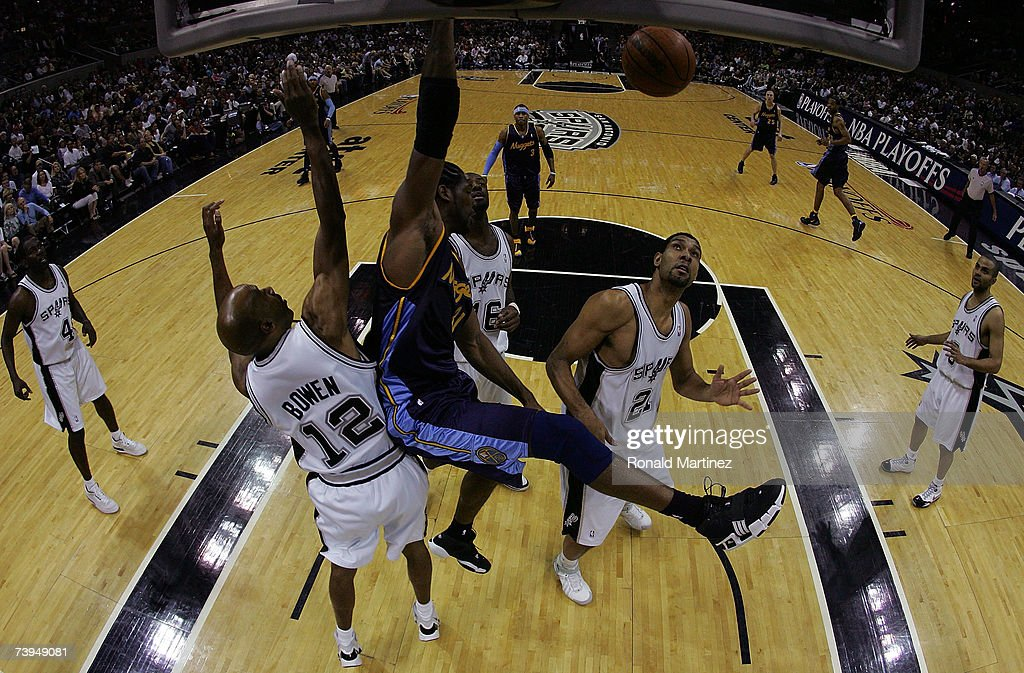 Forward Nene #31 of the Denver Nuggets gets a slam dunk against Bruce Bowen #12 and Tim Duncan #21 of the San Antonio Spurs in Game One of the Western Conference Quarterfinals during the 2007 NBA Playoffs at AT&T Center on April 22, 2007 in San Antonio, Texas.