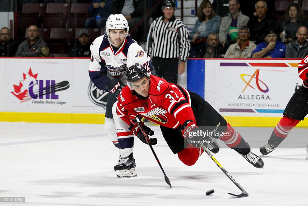 Forward Nick Suzuki #37 of the Owen Sound Attack moves the puck against forward Julius Nattinen #25 of the Windsor Spitfires on November 17, 2016 at the WFCU Centre in Windsor, Ontario, Canada.