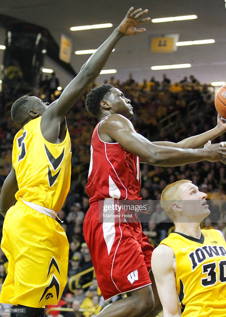 Forward <a gi-track='captionPersonalityLinkClicked' href=/galleries/search?phrase=Nigel+Hayes&family=editorial&specificpeople=11759753 ng-click='$event.stopPropagation()'>Nigel Hayes</a> #10 of the Wisconsin Badgers goes to the basket between guard Peter Jok #3 and forward <a gi-track='captionPersonalityLinkClicked' href=/galleries/search?phrase=Aaron+White+-+Basketball+Player&family=editorial&specificpeople=14619648 ng-click='$event.stopPropagation()'>Aaron White</a> #30 of the Iowa Hawkeyes, in the second half on January 31, 2015 at Carver-Hawkeye Arena, in Iowa City, Iowa.