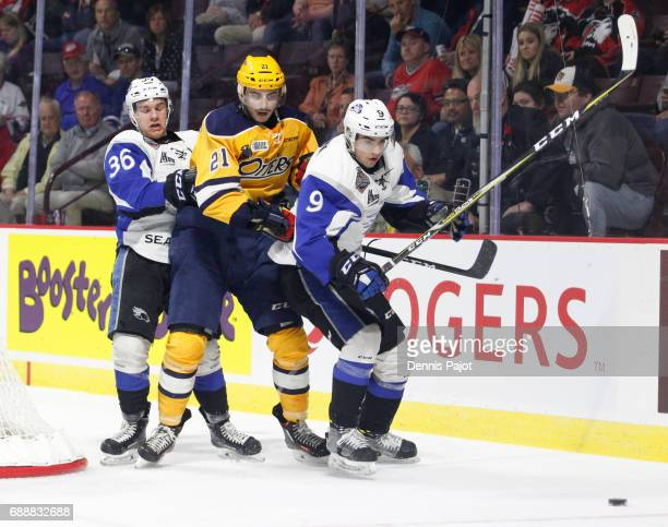 Forward Patrick Fellows of the Erie Otters battles for the puck against forward Joe Veleno and defenceman Alexandre Bernier of the Saint John Sea...