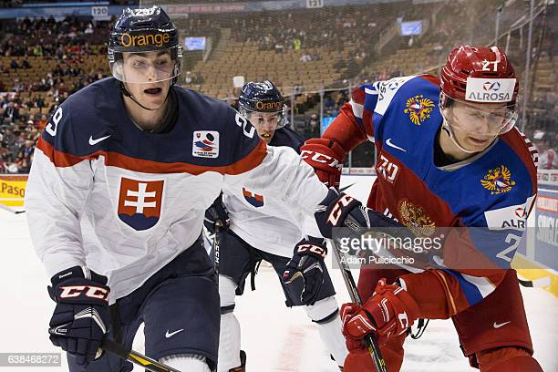 Forward Patrik Osko of Team Slovakia and forward Denis Guryanov of Team Russia battle for the puck in the corner in a preliminary round Group B game...