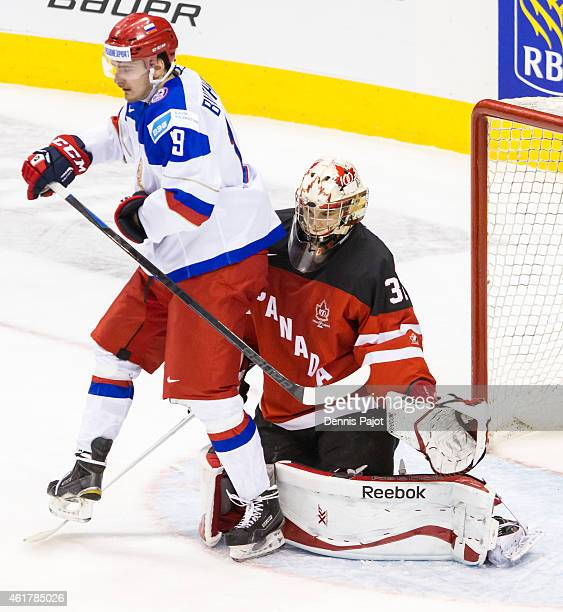 Forward Pavel Buchnevich of Russia battles for the puck against Zach Fucale of Canada during the Gold medal game of the 2015 IIHF World Junior...