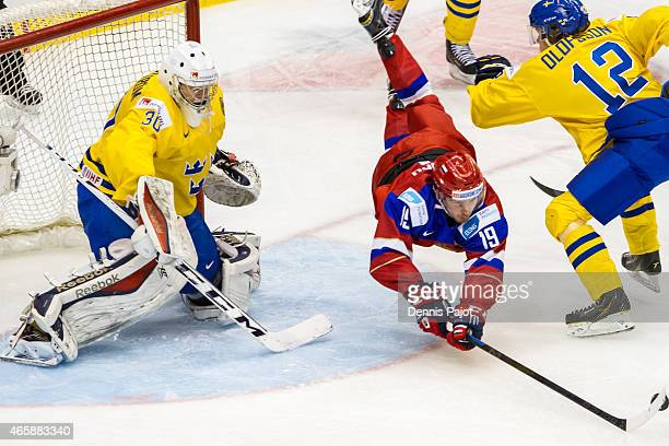 Forward Pavel Buchnevich of Russia is checked by forward Victor Olofsson of Sweden during the 2015 IIHF World Junior Championship on January 04 2015...