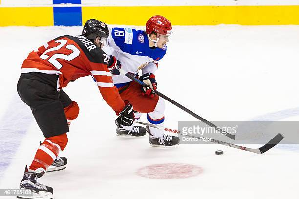 Forward Pavel Buchnevich of Russia moves the puck against forward Frederik Gauthier of Canada during the Gold medal game of the 2015 IIHF World...