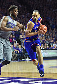 Forward Perry Ellis of the Kansas Jayhawks drives to the basket against forward Nino Williams of the Kansas State Wildcats during the first half on...
