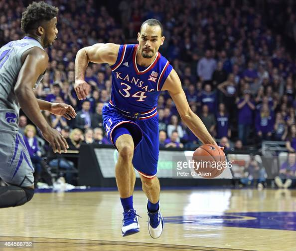 Forward Perry Ellis of the Kansas Jayhawks drives with the ball against forward Nino Williams of the Kansas State Wildcats during the first half on...