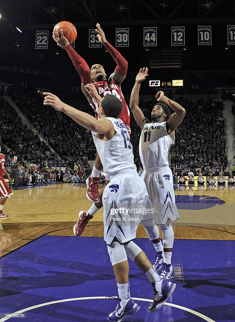 Forward Romero Osby #24 of the Oklahoma Sooners drives to the basket against defenders Nino Williams #11 and Angel Rodriguez #13 of the Kansas State Wildcats during the second half on January 19, 2013 at Bramlage Coliseum in Manhattan, Kansas. Kansas State defeated Oklahoma 69-60.