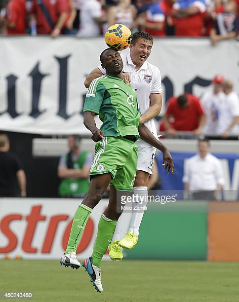 Forward Shola Ameobi of Nigeria goes up for a head ball against defender Matt Besler of the United States during the international friendly match at...