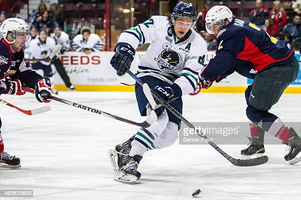 Forward Sonny Milano of the Plymouth Whalers moves the puck against defenceman Patrick Sanvido of the Windsor Spitfires on February 18 2015 at the...