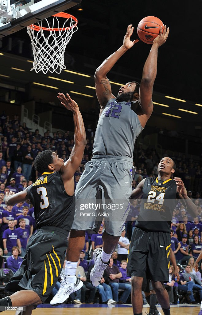 Forward Thomas Gipson #42 of the Kansas State Wildcats scores over guard Juwan Staten #3 of the West Virginia Mountaineers during the second half on February 18, 2013 at Bramlage Coliseum in Manhattan, Kansas. Kansas State defeated West Virginia 71-61.
