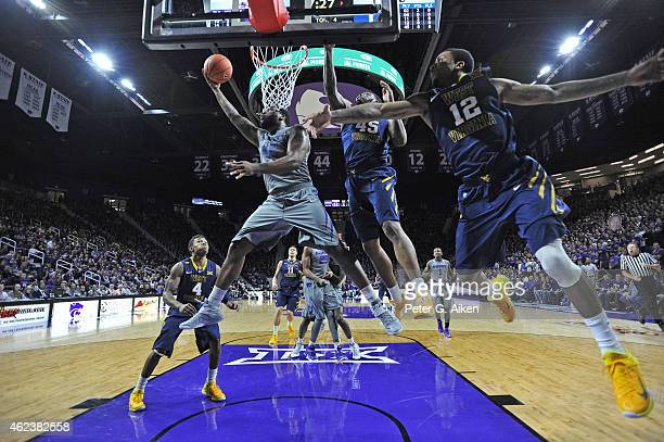 Forward Thomas Gipson of the Kansas State Wildcats scores past defenders Eluah Macon and Tarik Phillip of the West Virginia Mountaineers during the...