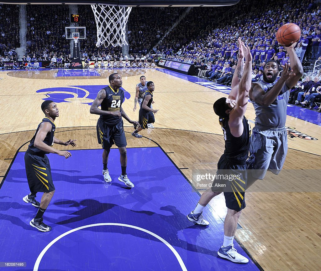 Forward Thomas Gipson #42 of the Kansas State Wildcats shoots over forward Deniz Kilicli #13 of the West Virginia Mountaineers during the first half on February 18, 2013 at Bramlage Coliseum in Manhattan, Kansas. Kansas State defeated West Virginia 71-61.