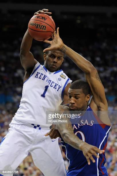 Forward Thomas Robinson from the University of Kansas and guard Darius Miller from the University of Kentucky battle for control of a loose ball...