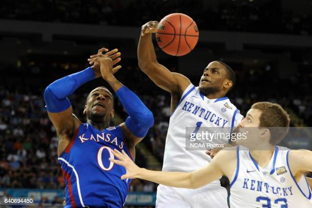Forward Thomas Robinson from the University of Kansas battles for control of a loose ball against guard Darius Miller from the University of Kentucky...