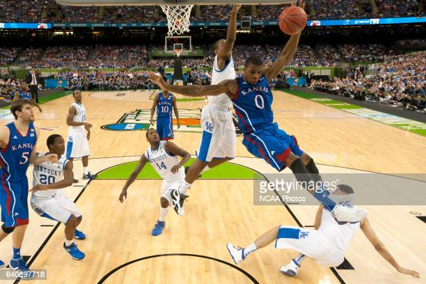 Forward Thomas Robinson from the University of Kansas is upended by the defensive play of teammates guard Darius Miller and forward Eloy Vargas from...