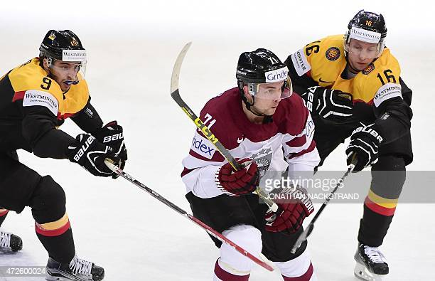 Forward Tobias Rieder and forward Michael Wolf of Germany vie for the puck with forward Roberts Bukarts of Latvia during the group A preliminary...
