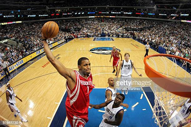 Forward Tracy McGrady of the Houston Rockets makes a windmill dunk against Michael Finley of the Dallas Mavericks on January 12 2005 at the American...