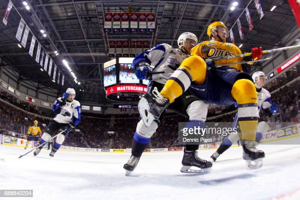Forward Warren Foegele of the Erie Otters battles in front of the net with defenceman Jakub Zboril of the Saint John Sea Dogs on May 26 2017 during...
