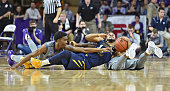 Forward Wesley Iwundu of the Kansas State Wildcats reaches for the ball on the floor against guard Gary Browne of the West Virginia Mountaineers...