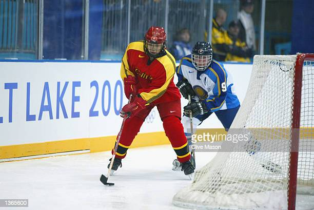 Forward Xiuqing Yang of China skates with the puck while being pursued by defender Olga Potapova of Kazakhstan during their game at the Salt Lake...