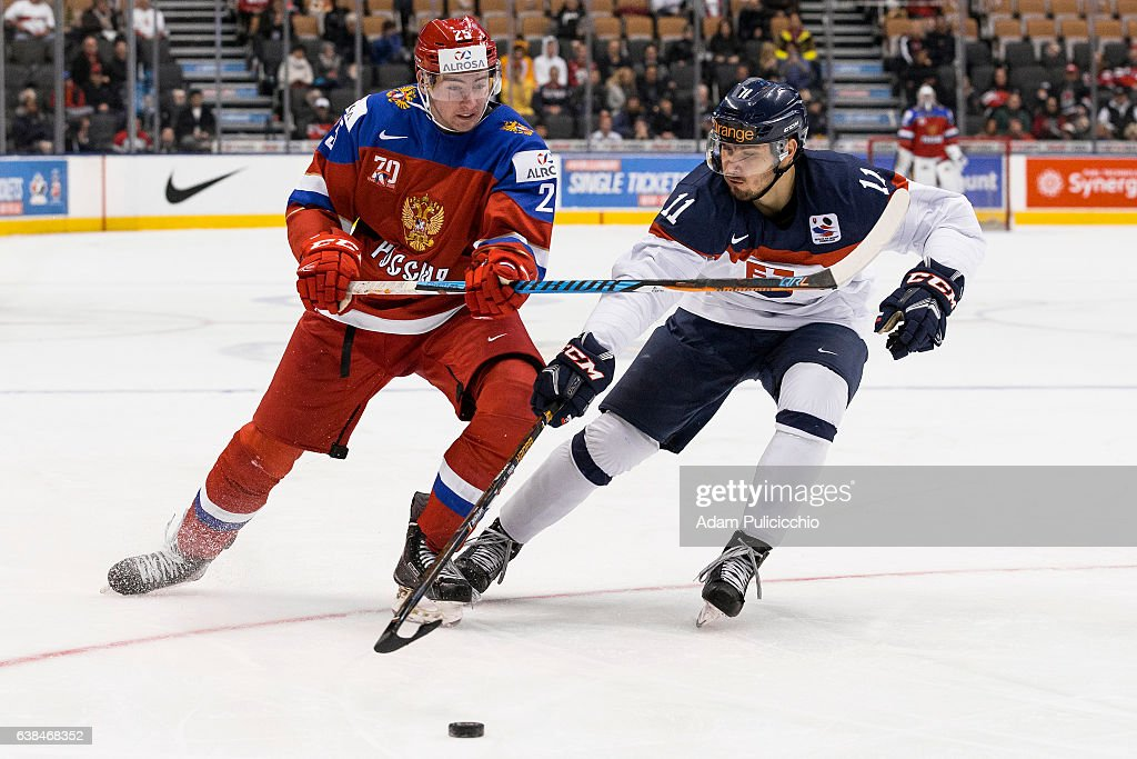 Forward Yakov Trenin #25 of Team Russia and Assistant Captain forward Radovan Bondra #11 of Team Slovakia fight for puck possession in a preliminary round - Group B game during the IIHF World Junior Championship on December 31, 2016 at the Air Canada Centre in Toronto, Canada.