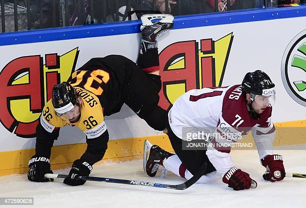 Forward Yannic Seidenberg of Germany is tackled by forward Roberts Bukarts of Latvia during the group A preliminary round match Germany vs Latvia at...