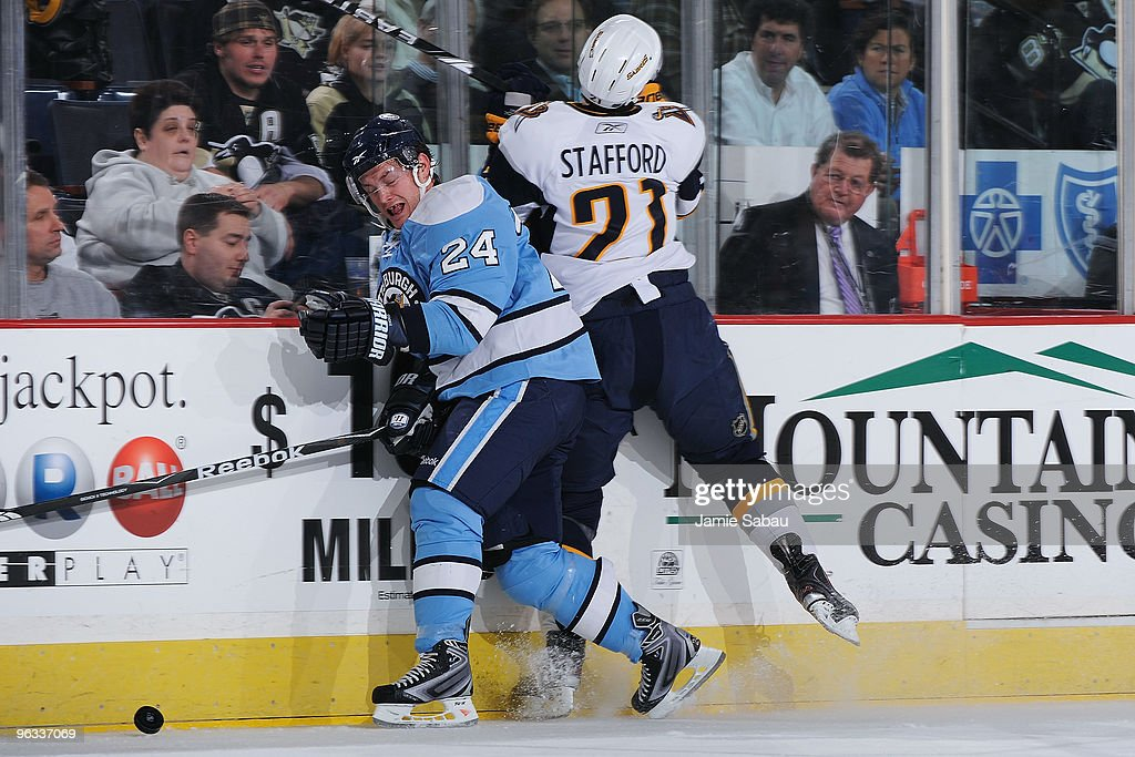 Forwards Matt Cooke of the Pittsburgh Penguins and Drew Stafford of the Buffalo Sabres crash into the boards as they chase down a loose puck in the...