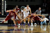 Forwards Taylor Griffin and Blake Griffin of the Oklahoma Sooners scramble for a loose ball against forward Luis Colon of the Kansas State Wildcats...