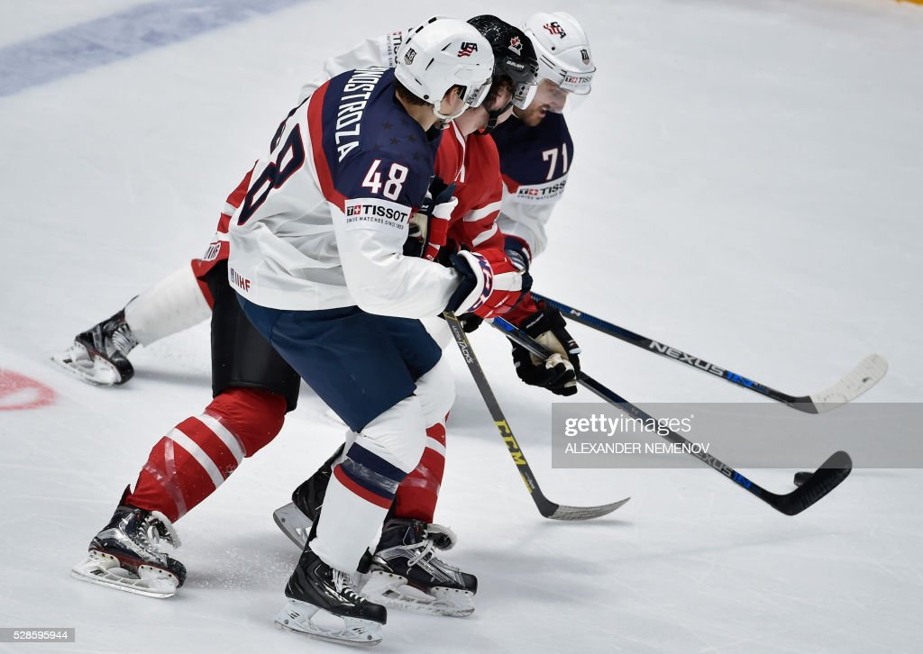 US forwards Vince Hinostroza (L) and Nick Foligno (R) vie with Canada's defender Ben Hutton during the group B preliminary round game USA vs Canada at the 2016 IIHF Ice Hockey World Championship in St. Petersburg on May 6, 2016. / AFP / ALEXANDER