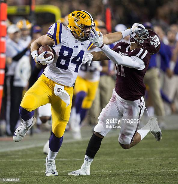 Foster Moreau of the LSU Tigers gives a stiffarm as Larry Pryor of the Texas AM Aggies grabs him by he face mask at Kyle Field on November 24 2016 in...