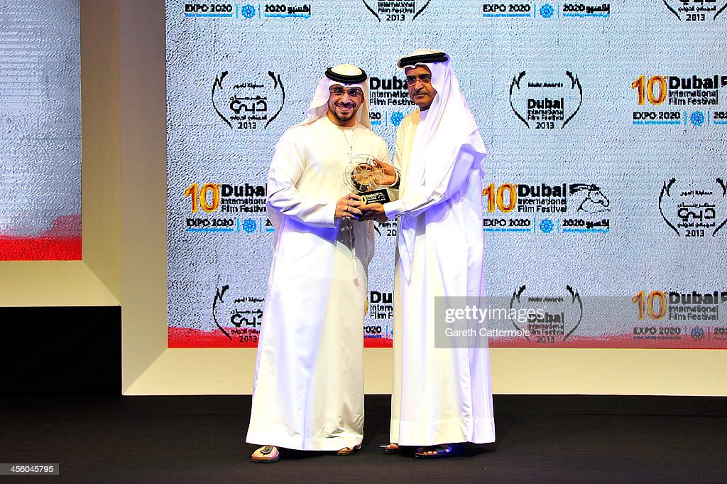 Fouad Baroudi (L) is presented with his award by DIFF Chairman Abdulhamid Juma at the Muhr Awards during day eight of the 10th Annual Dubai International Film Festival held at the Madinat Jumeriah Complex on December 13, 2013 in Dubai, United Arab Emirates.
