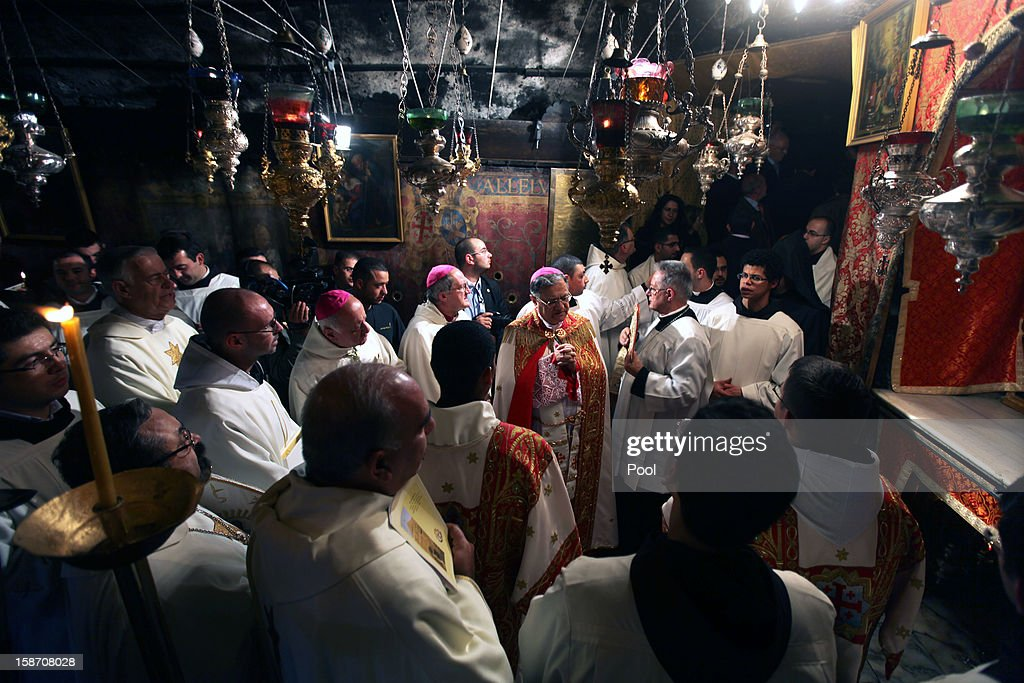 Foud Twal (C), the Latin Patriarch of the Holy Land, and clergy pray in the Grotto, where Christians believe the Virgin Mary gave birth to Jesus Christ, in the Church of the Nativity at the conclusion of the Midnight Mass on December 25, 2012 in Bethlehem, West Bank. Thousands of pilgrims made their way to the Church of the Nativity this week to worship at the sacred site believed to be the birthplace of Jesus.