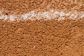 A close up shot of a messed up foul ball white chalk line on a little league baseball field at a local public park.