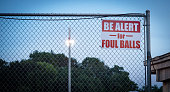 A warning sign alerts people to the risk of foul balls at a sports field.